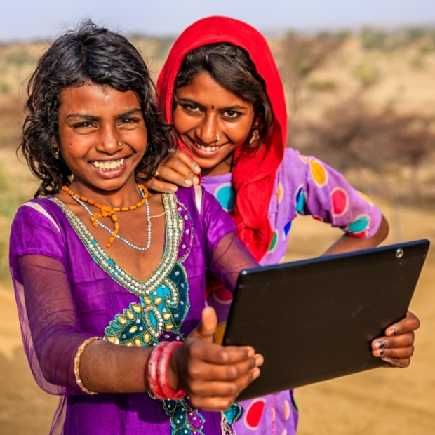 Happy Indian girls in desert with tablet, iStock image.