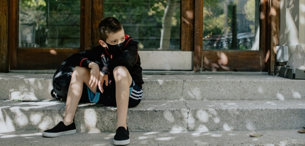 child sitting in front of school