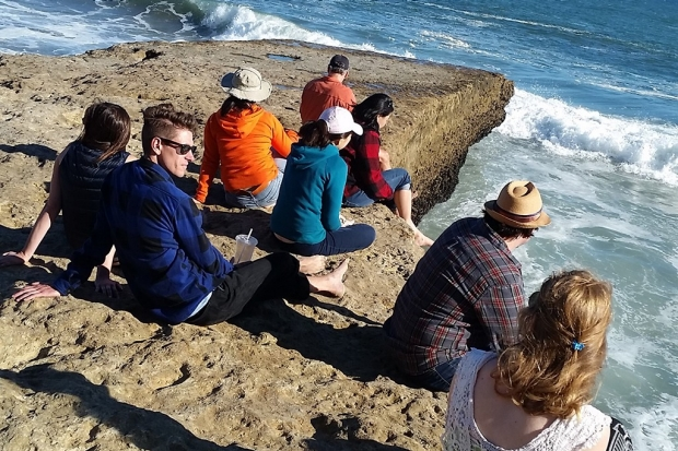 group sitting at Pacific coast shoreline