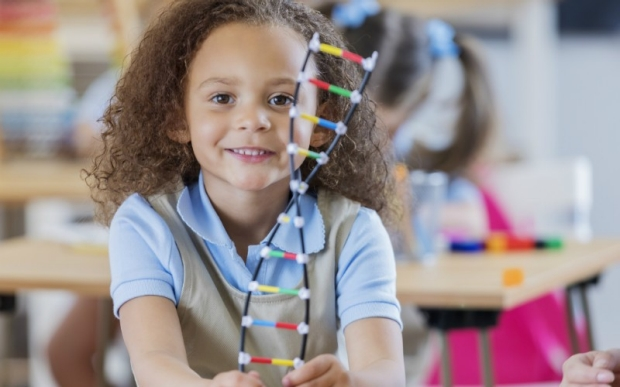 Young girl with plastic DNA strand toy