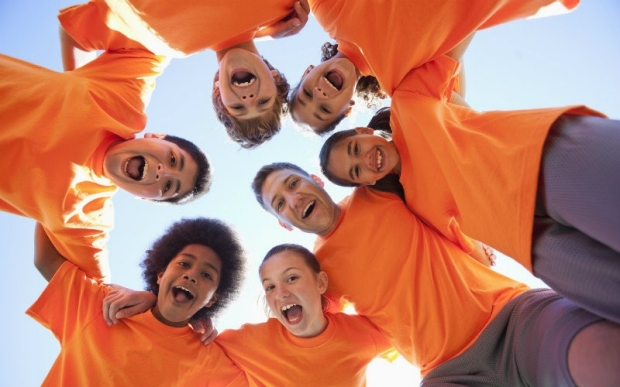 Kids in orange shirts in a circle with their coach