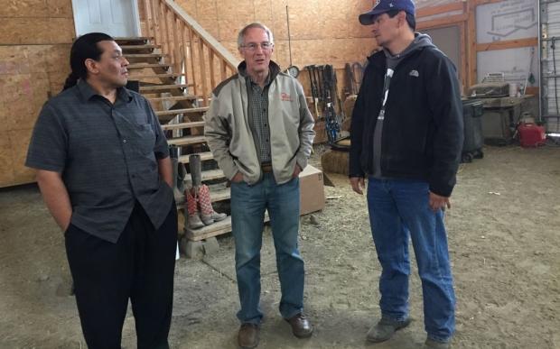 Three men standing in a workroom