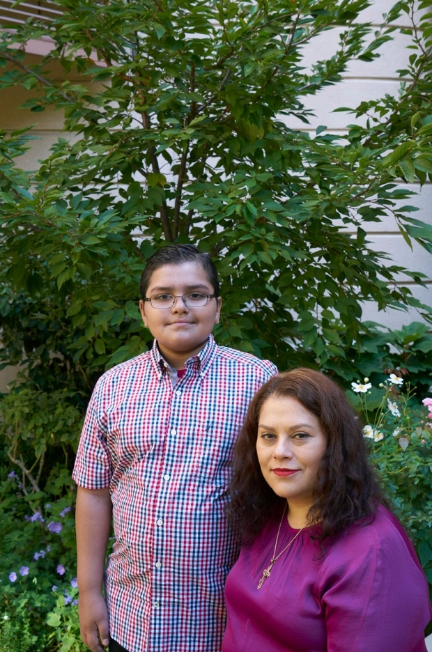 Teenage boy standing next to his mother