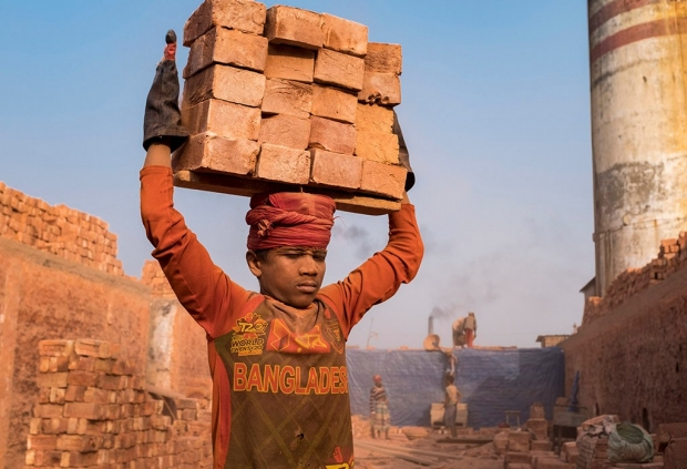 A worker in Bangladesh carried newly fired bricks