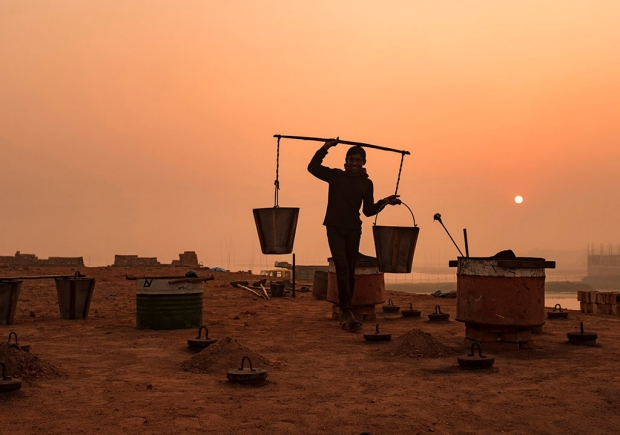 A worker carries buckets of coal to the kilns