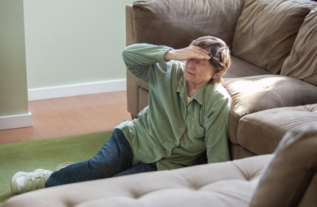 An eldery woman with vertigo sitting on the floor and touching her forehead