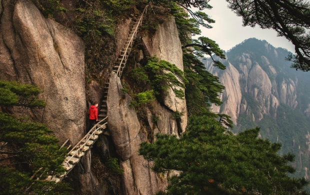 man on ladder type wooden stairs on the side of a cliff stands for a moment before going up perhaps