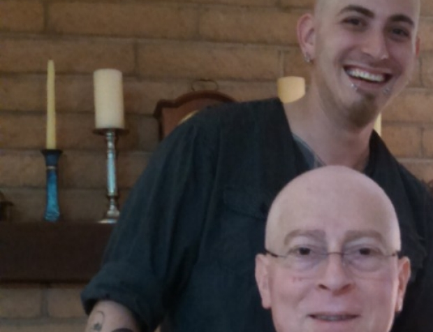 Father and Son in their living room - the son has shaved his head in solidarity!