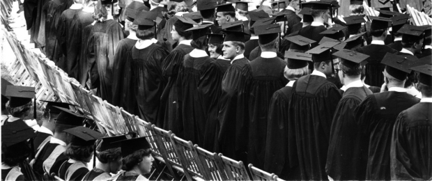 A black and white picture shows a couple looking back into the crowd during a graduation ceremony