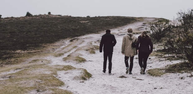 three people with backs turned walking towards a vista on a snow swept walkway with winter grey