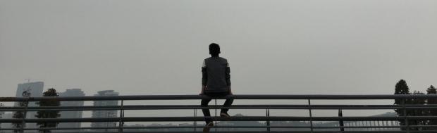 man sitting alone on a fence