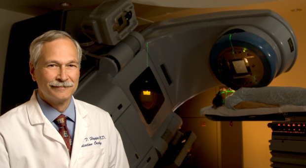 Richard Hoppe, MD, professor of radiation oncology, with a modern medical linear accelerator