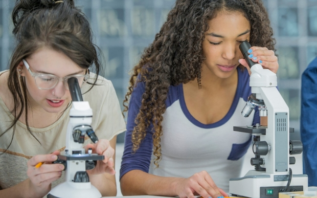 Two high school girls peer through microscopes