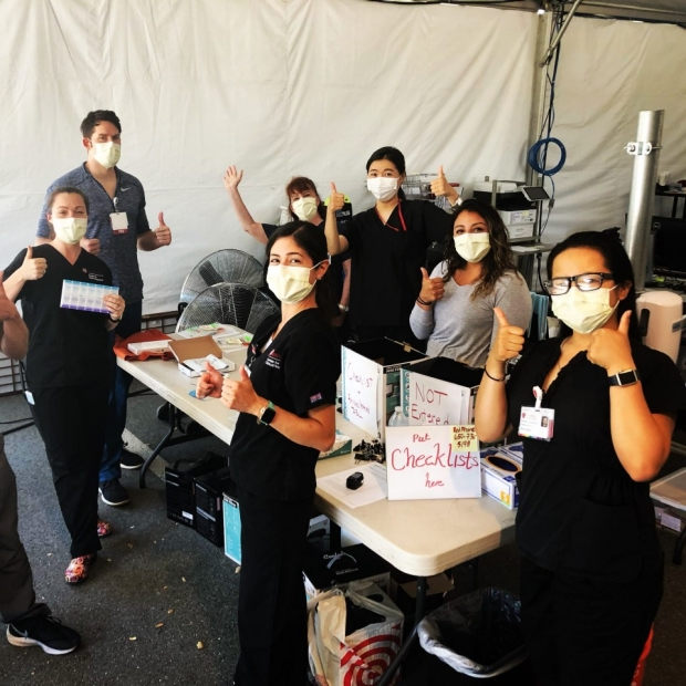 Picture of masked group of researchers dressed in black, giving thumbs up, courtesy of Stanford Daily