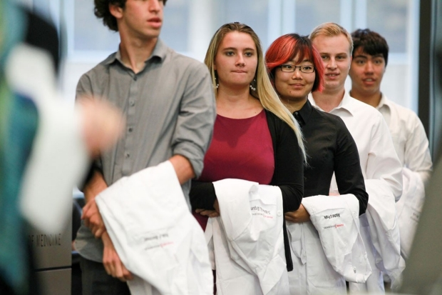 Graduate students at white coat ceremony