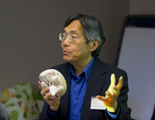 Alan Louie holding a model of a brain