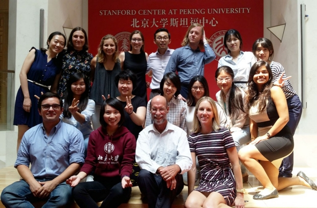 Faculty and students in front of a banner for Stanford Center at Peking University
