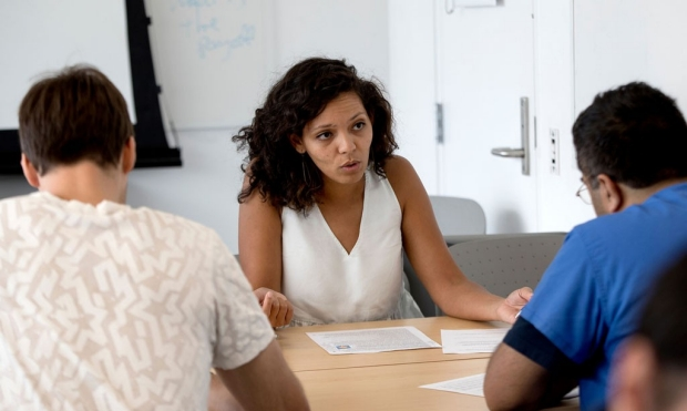 Woman talking to two students working on grant applications