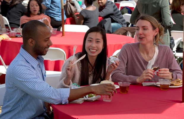 Man and two women seated at a table during a staff barbecue