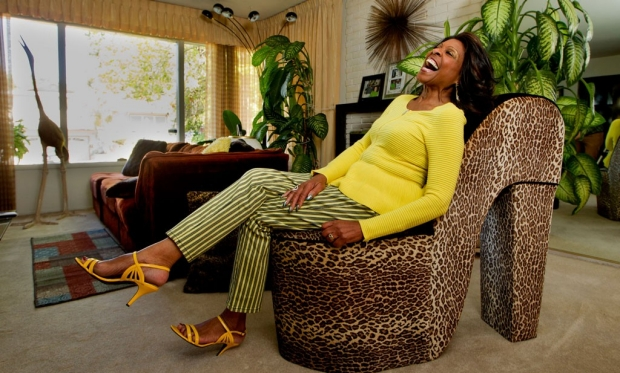 Woman laughing as she sits on a shoe-shaped chair