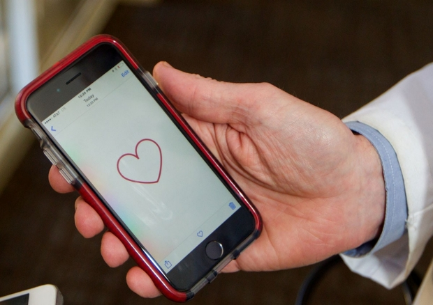 Hand holding a smartphone displaying the MyHeart Counts app