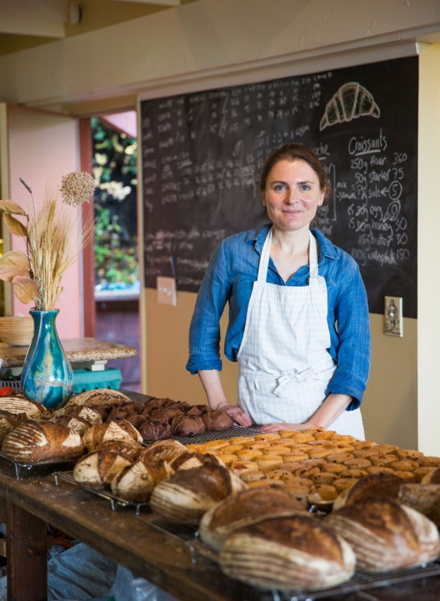Woman in an apron standing behind a counter of bread