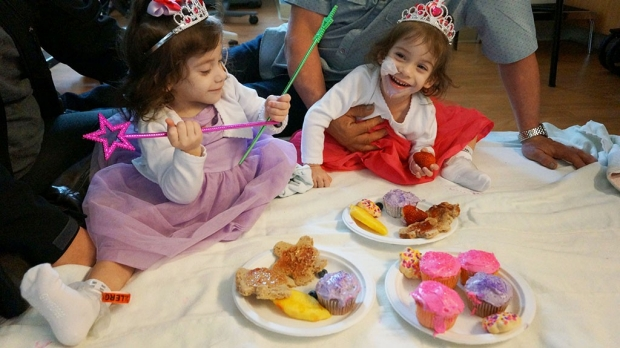 Twin toddlers in princess outfits eating cupcakes and treats