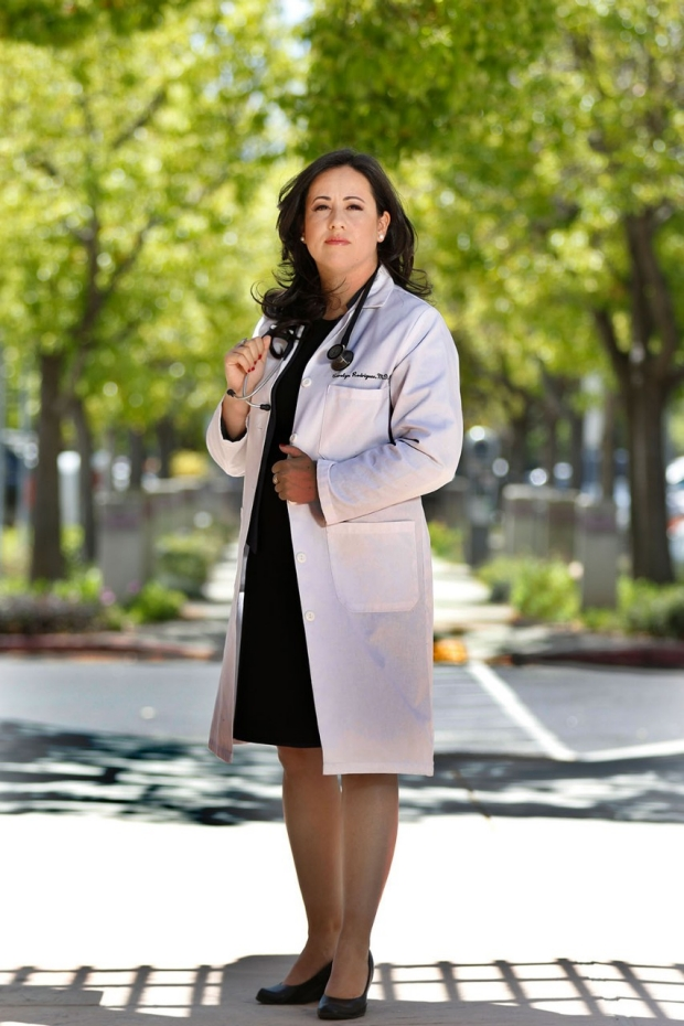 Woman in a white lab coat standing on a sidewalk in front of trees