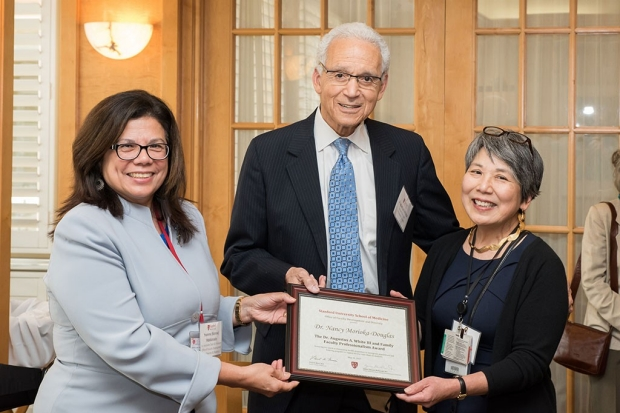 A woman and a man presenting a plaque to a woman