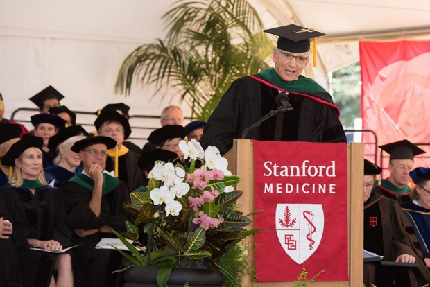 Man in a cap and gown speaking to medical school graduates