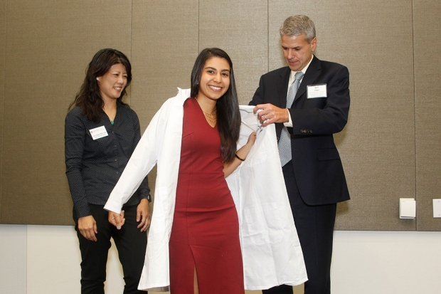 Student Stephanie Kabeche puts on lab coat