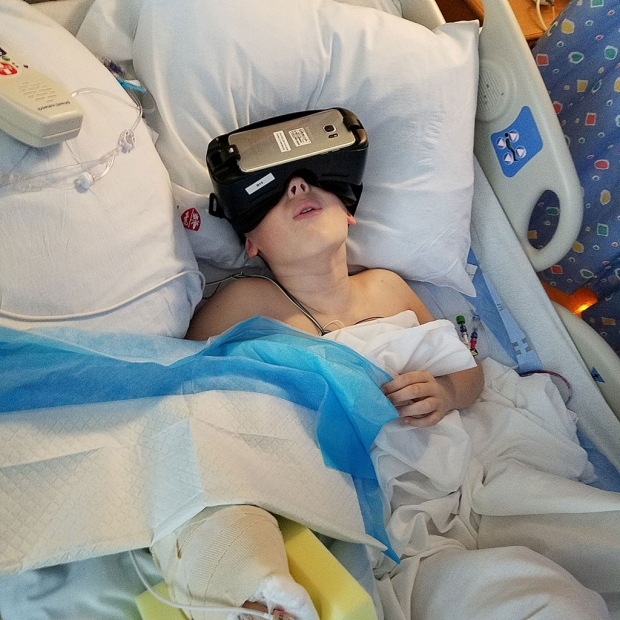 Child lying in a hospital bed, wearing virtual-reality goggles