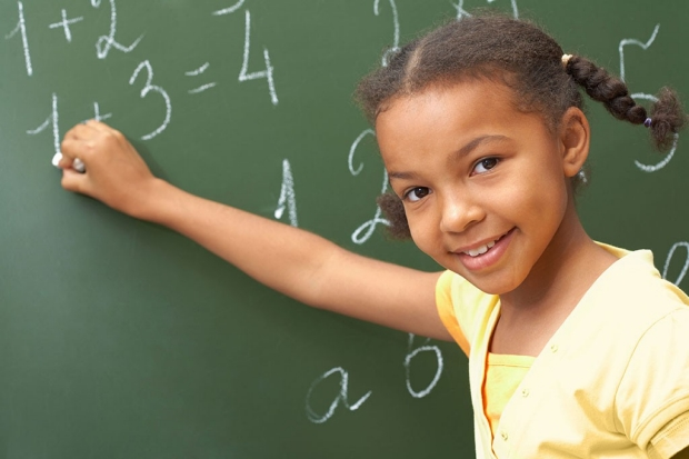 Happy young girl doing math on a chalkboard