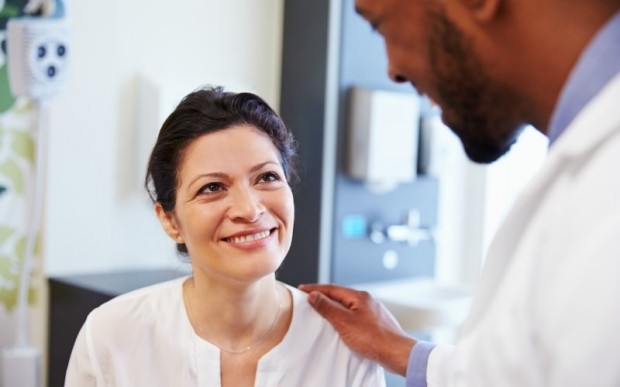 Smiling woman being reassured by a doctor